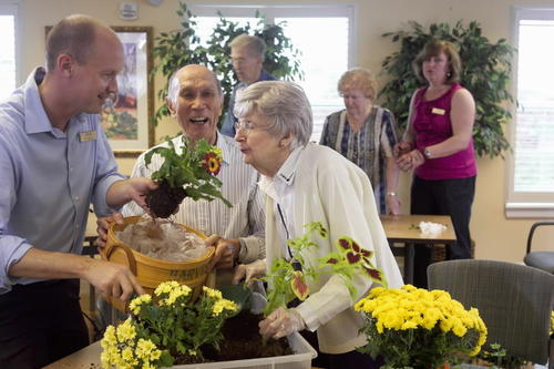 Residents at Belmont Village in Buffalo Grove, Illinois, participate in an activity with plants and flowers that is designed to stimulate long-term memory.