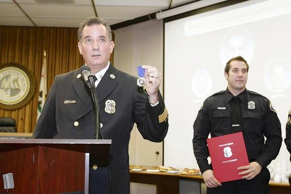 Newport Beach Fire Chief Scott Poster, left, holds up the Medal of Valor Award before presenting it to Firefighter Bryce Anderson, right, during the 2012 Honor Awards on Thursday.