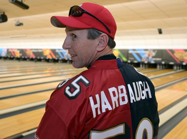 Craig Steichen poses with a half San Francisco 49ers and half Baltimore Ravens jersey both bearing the name Harbaugh at the eighth annual NFL Foundation Celebrity Bowling Classic.