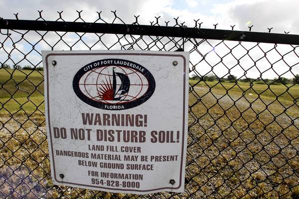 Fences and signs ward off trespassers at the former Wingate incinerator site in Fort Lauderdale.