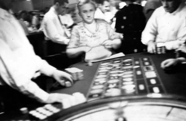 The elderly woman at the end of the roulette table remained in her seat all afternoon at the Dev-Lin gaming house in Lincolnwood in August 1935. A large stack of new bills lies near the croupier's left hand.