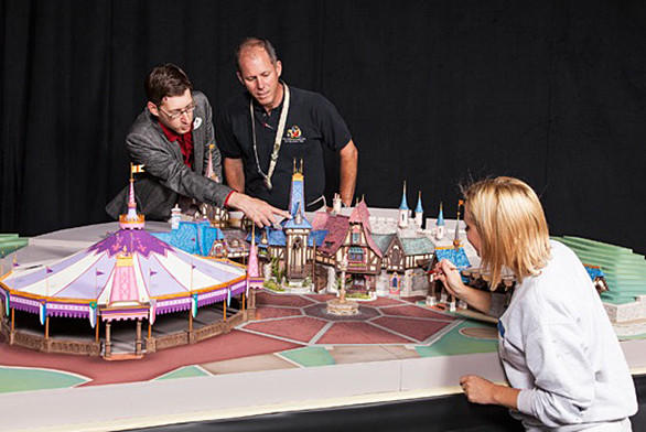 Walt Disney Imagineers look over a scale model of Fantasy Faire enchanted village coming to Disneyland in March.