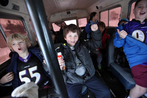Jackson Coates, left, Adam Snyder, center, and Stephen Hook III, right, show off their Ravens gear while getting dropped off to St. Mark's School.
