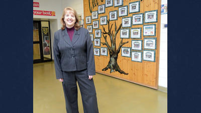 Turkeyfoot Valley Area School District Superintendent Darlene M. Pritt stands in front of The Tree of Excellence, an area in the school's main foyer where student honors, achievements and attendance are acknowledged.