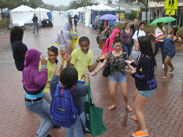 Students from Victory Prep Christian Academy dance in the light rains on Kennedy Blvd. They are dancing to historic Motown hits. The first day of the Zora Neale Hurston festival in Eatonville started with sprinkles on the many school kids who came to learn about black heritage and the great writer.
