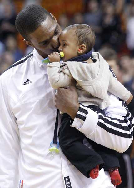 The Miami Heat's Chris Bosh holds his child on the court as the arena observed a moment of silence for the victims of the Sandy Hook Elementary School shooting in Newtown, Connecticut before playing the Washington Wizards in this NBA basketball game in Miami, Florida December 15, 2012.