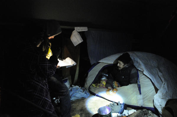 Cecelia Peppers-Johnson, of Hartford, left, and Jacob Aparicio of Glastonbury interview  Alfredo Rivera, right, who was spending the night in a tent under a highway overpass near downtown Hartford Tuesday night.