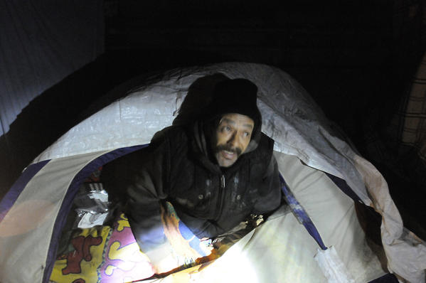 Alfredo Rivera, who was spending the night in a tent under a highway overpass near downtown Hartford Tuesday night, talks to homeless census takers who were doing an annual homeless count in Hartford.