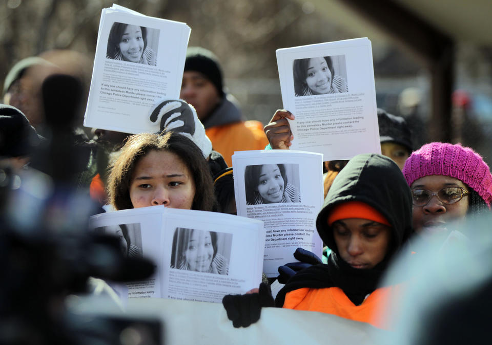 A small group of people march between King College Prep High School and Vivian Gordon Harsh Park in Chicago carrying flyers that show Hadiya Pendleton, was shot and killed in the park several days earlier.
