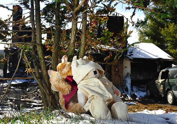 A pair of teddy bears sit beneath an evergreen tree in the front yard of a home where two young girls died in a fire Thursday night.