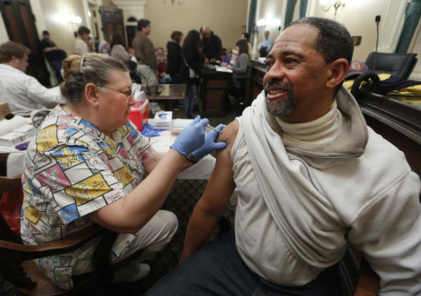 Claude Flanagan receives a flu shot from Geneva Hill, a licensed vocational nurse, during a free flu vaccine clinic this week in Sacramento. This season's outbreak, though still strong, appears to be waning, the CDC says.