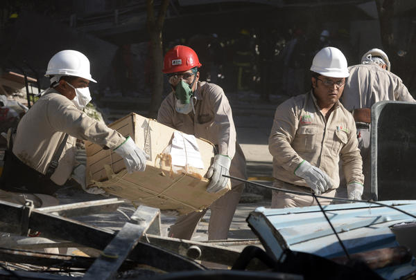 Pemex workers remove items from the headquarters of the state-owned Mexican oil company in Mexico City on Friday after an explosion the day before.
