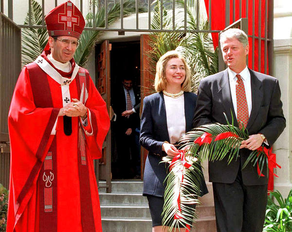 President Bill Clinton and First Lady Hillary Rodham Clinton attend a Catholic Palm Sunday service in Los Angeles with Cardinal Roger Mahony in 1995.