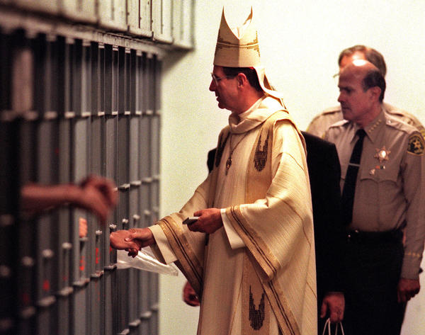 Cardinal Roger Mahony extends a Christmas greeting for prisoners at L.A. County Central Jail after saying Mass in the chapel earlier. Accompanying him is Sheriff Lee Baca, right.