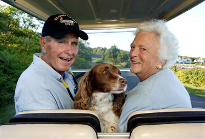 George H. W. Bush and wife, Barbara Bush, cruise in the back of a golf cart with their dog Millie.