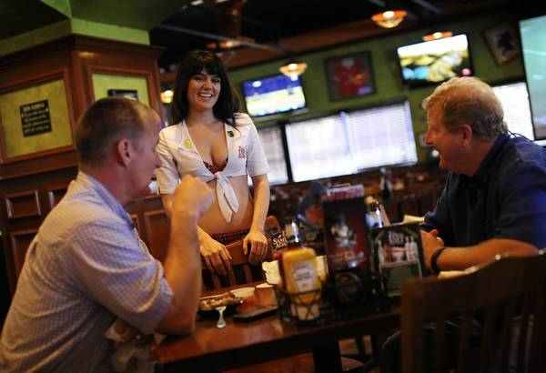 Tilted Kilt Pub & Eatery server Aileen Suseck waits on Rick Paulk, left and Peter Buell, right, at the restaurant on International Drive on January 30, 2013.