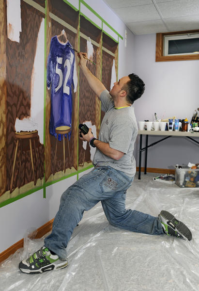 Propst paints a Ravens locker-room mural, one of two Ravens murals in Ken Davis' basement game room.