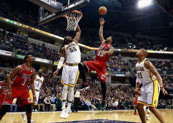 Miami Heat forward Udonis Haslem (2nd R) shoots while Indiana Pacers center Roy Hibbert (55) defends as Pacers center David West (21) and Heat forward Christ Bosh (1) watch during the first quarter of their NBA basketball game in Indianapolis, Indiana February 1, 2013.