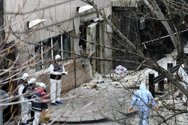 Investigators inspect the scene of the bombing at the U.S. Embassy in Ankara, Turkey. Among the injured was a Turkish television journalist who was visiting the American ambassador.