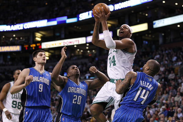 Boston Celtics small forward Paul Pierce (34) drives the ball against Orlando Magic point guard Jameer Nelson (14) and small forward DeQuan Jones (20) during the first quarter at the TD Garden.