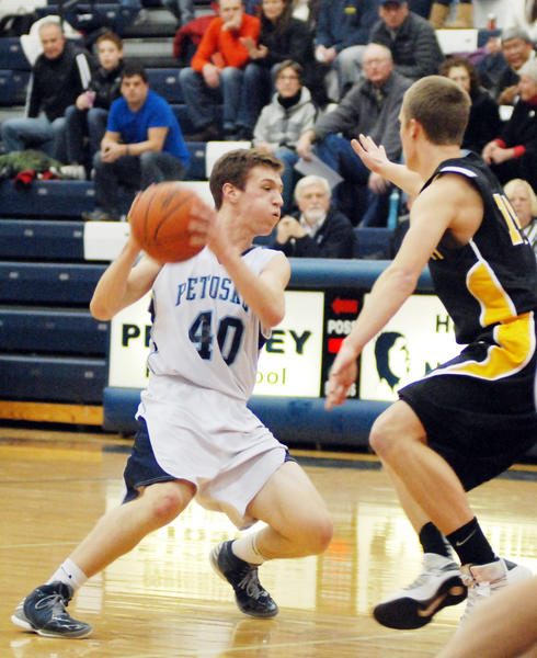 Petoskey junior forward Shea Whitmore (left) looks inside as Traverse City Central's Colin Lesoski defends during Friday's Big North Conference contest at the Petoskey High School gym. The Northmen defeated the Trojans, 63-46.