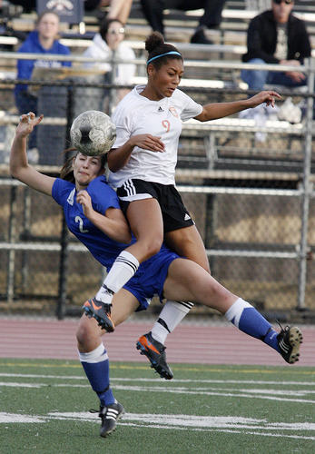 South Pasadena's Kelly Brady jumps over and tangles up with San Marino defender Avery Barth in the second half of a Rio Hondo League girls soccer match at South Pasadena High School in a on Friday, February 1, 2013. The game ended in a 2-2 tie.