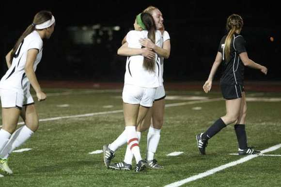 Flintridge Sacred Heart Academy's Hailey James, top center, embraces Savannah Viola after scoring in a 3-2 Mission League win over Harvard Westlake.