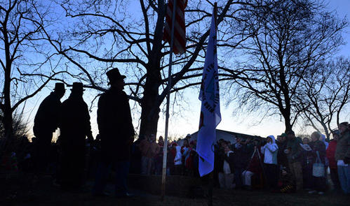Led by members of Grundsau Lodsch 16, left, people sing The Battle Hymn of the Republic at sunrise. This was at the annual Grundsau Lodsch Number 16 of Schnecksville Goundhog Day event held at Wehr's Dam Covered Bridge Park at sunrise Saturday. In the opinion of Yahdee the lodge's groundhog there will be some cold days and there will be some warm days ahead which means people can start their gardens and plant their peas on St. Patrick's Day in March.