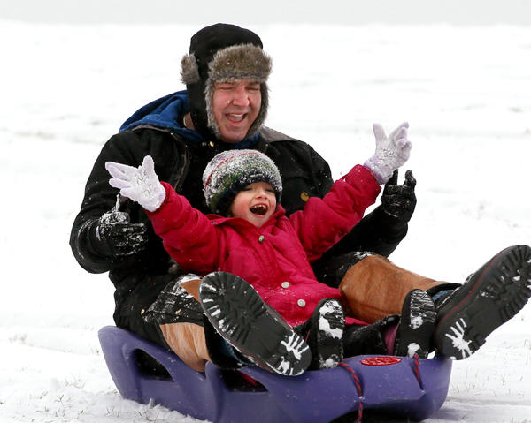 Johann Kirschinger and his daughter Lucia, 4, slide down a hill at Henry C. Palmisano Nature Park in Chicago on Saturday.