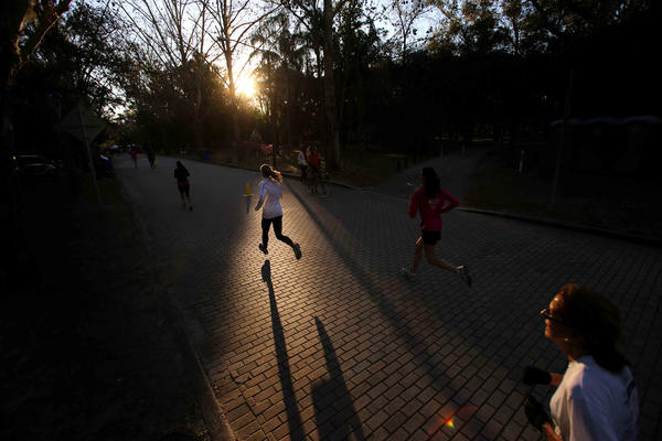 Runners come down the final stretch as the rising sun peeks through the trees duringt the Lady Track Shack 5k in Winter Park, Fla.