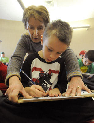 Anne Marie Cohen of Emmaus (back) helps her grandson Hunter Smith 6, of Barto, (front) as he makes a Superhero bookmark during a workshop with Marvel/DC Artist Bob McLeod at the Emmaus Public Library during day two of the Emmaus Arts Commission SnowBlast Winter Festival Saturday.