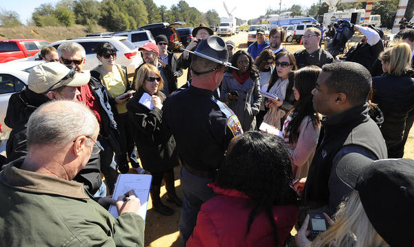 An Alabama state trooper is surrounded by reporters after a news conference in Midland City, Ala. Authorities said they still have an open line of communication with an Alabama man accused of abducting a 5-year-old child and holding him hostage in a bunker since Tuesday.