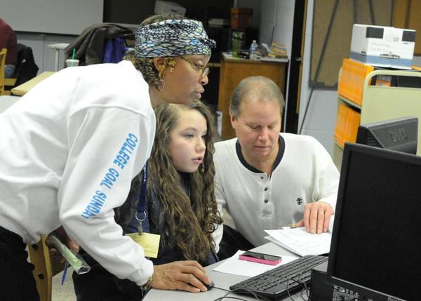 Karen Saint John, school/career counselor at New Britain High school, helps Katrina Sadlowski and her father, David Sadlowski, go through the FAFSA process.