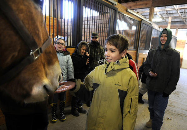 Sam Neville, 11, of Avon gives Hannibal a treat during the 1st of 10 monthly lessons for children of deployed soldiers. The lessons are held at the First Company Governor's Horse Guard in Avon. At right is Jacob Avery, 15, of Windham.