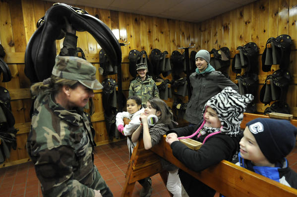 Holding up a saddle, instructor Corporal Laurel Urda jokes with her students, Zeala Crespo, 6, of New London, Suzannah Neville, 8, of Avon, Dhalia Mae, 7, of Shelton and Griffin Albaugh, 8, from New Milford during a lesson in the tack room at the First Company Governor's Horse Guard stable.