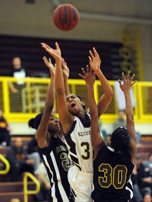 Kutztown's Advia Campbell (center) drives to the basket in between Bloomsburg's Adreana Sadowski (left) and teammate Marla Simmons (right) during their college women's basketball game.