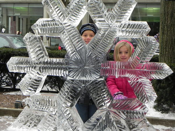 Brandis Martin, 6, and his sister Rylee, 5, of Chambersburg, Pa., pose with an ice snowflake at IceFest on Saturday.