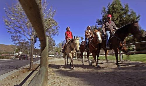 "Lori Hall, her daughter Ali and friend Edward ""Buzz"" Riebschlager ride along the dirt trails off Sixth Street in Norco. Most of Norco's neighborhoods are connected by horse trails."