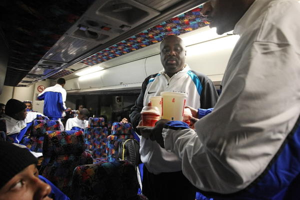 Simeon coach Robert Smith passes out Wendy's orders on a bus following a game in Tennessee earlier this season.
