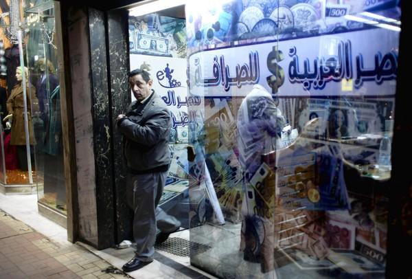 A man leaves an exchange office in Cairo last month after changing foreign currency. At the heart of the discontent in Egypt is the public anger over the battered economy.