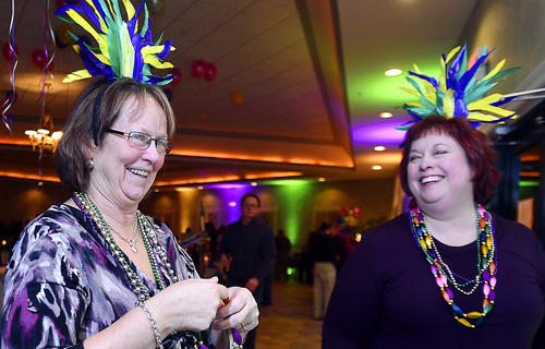 Cheri Noll, left, of Waynesboro buys beads and a festive feather headdress from W House board member Anne MacMillan Saturday during the Mardi Gras theme fundraiser event benefiting the W House at the Cortland Mansion Saturday in Hagerstown.