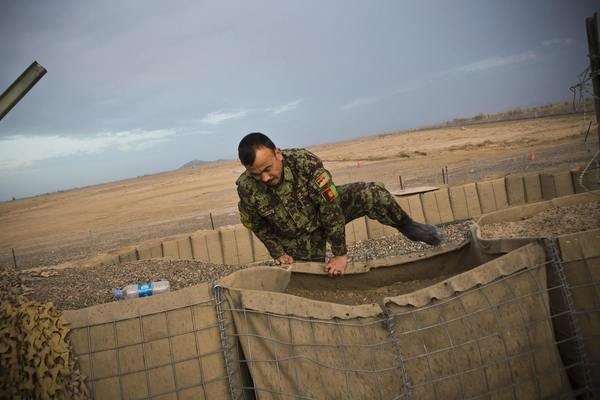 A soldier in the Afghan National Army jumps from a guard tower to inspect a local resident they considered suspicious, who was found walking near Command Outpost AJK, in Maiwand District, Kandahar Province