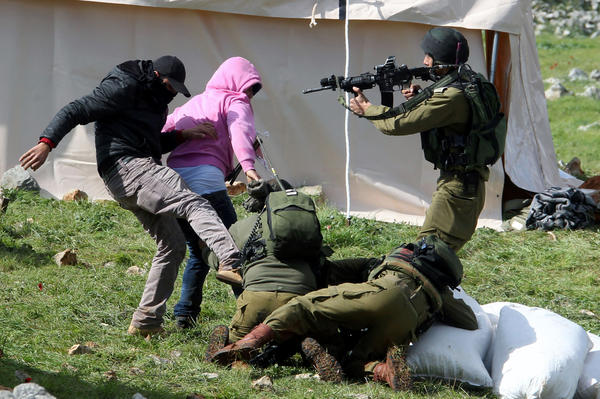Palestinian protesters resist arrest by Israeli soldiers as they forcefully remove demonstrators from a new camp set up to protest against Jewish settlements near the West Bank village of Burin.