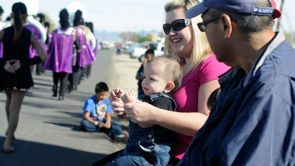 Tiffany Cadiz and her 16-month-old son, Zander Cadiz, watch the Tomato Festival Parade on Saturday morning in Niland.