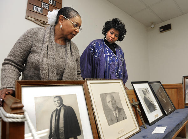 In the upper sancturary on the third floor of the Asbury United Methodist Church, Gloria Brown, church historian, left, and Dr. Carletta Allen, pastor, look at portraits of former pastors. At left on the original church pew is a photograph of Rev. Hilton A. Parker. Second from left is Bishop Edgar A. Love. Asbury United Methodist Church on 87 West St. is the oldest African American Church in Annapolis, if not in Anne Arundel County. Its leaders are planning an exhibit on its history for later this year, in part using a $2,500 matching grant from the area's heritage organization.