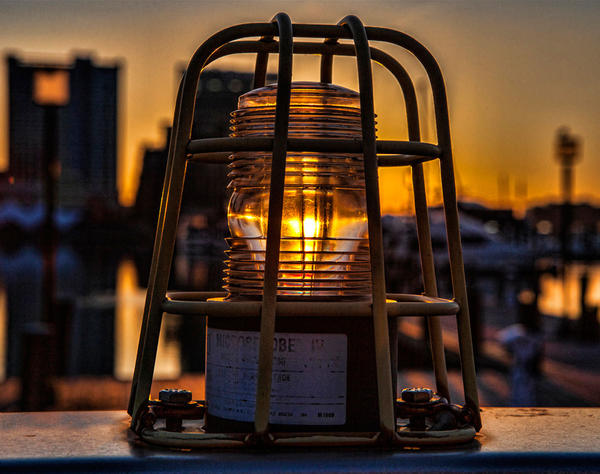"Honorable mention for this week's Reader SunShots series ""Shiny"" goes to Deborah Felmey for her picture of a strobe light along the Inner Harbor lit up by the rising sun. The photo was shot with a Canon 5D Mark II camera. Here is a critique by director of photography Robert Hamilton: ""The photographer demonstrated good vision with the picture. Lining up the strobe and the sun made the picture much more interesting. She also kept just enough of the background in focus to give the viewer a sense of place."""