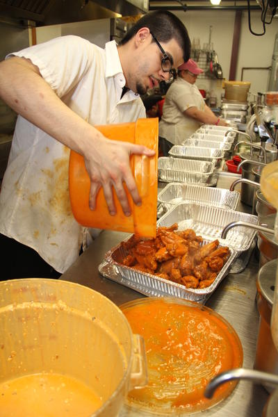 Line cook Erik Sicairos fills an order of spicy wings Sunday afternoon at Sliders Grill & Bar, 950 Yale Ave., Wallingford. The kitchen will cook close to 14,000 chicken wings on Super Bowl Sunday to fulfill its orders, according to kitchen manager Aaron Kemp.