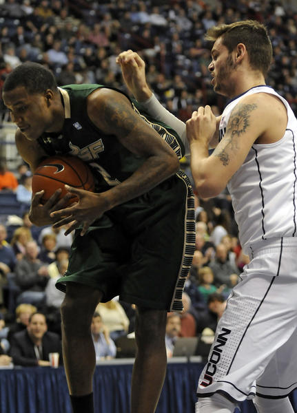 South Florida forward Toarlyn Fitzpatrick grabs a rebound away from UConn center Enosch Wolf during the first half at Gampel Pavilion Sunday afternoon. Fitzpatrick scored 22 points for the Bulls, but Wolf and the Huskies pulled out a 69-64 OT victory.