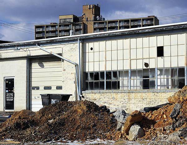 The former Massey Auto Body building, the largest structure on the property with 120,000 square feet of space, and a pair of two-story brick residential buildings have fallen into disrepair over the years, and questions remain about what can be done with them.