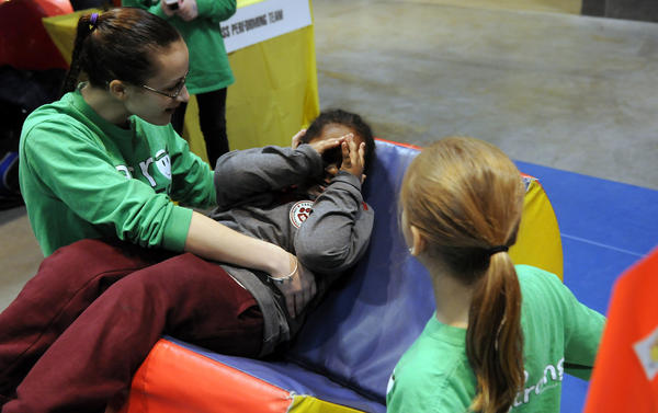 Joshua Brown, 3, of Hartford peeks out from behind his hands as Kristin Visciotti, 15, of Simsbury and Kelly Severance, 11, of Granby, show him a little ride they have as part of Acro Fitness/ Playstrong a the 9th Annual Big Y Kids Fair Saturday and Sunday at the Connecticut Convention Center in Hartford.